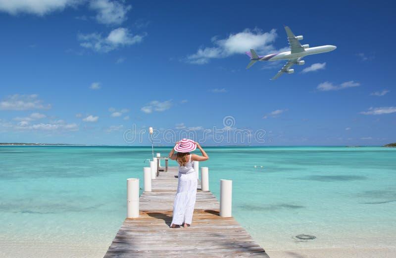Κορίτσι στον ξύλινο λιμενοβραχίονα που κοιτάζει στον ωκεανό στοκ εικόνα με δικαίωμα ελεύθερης χρήσης