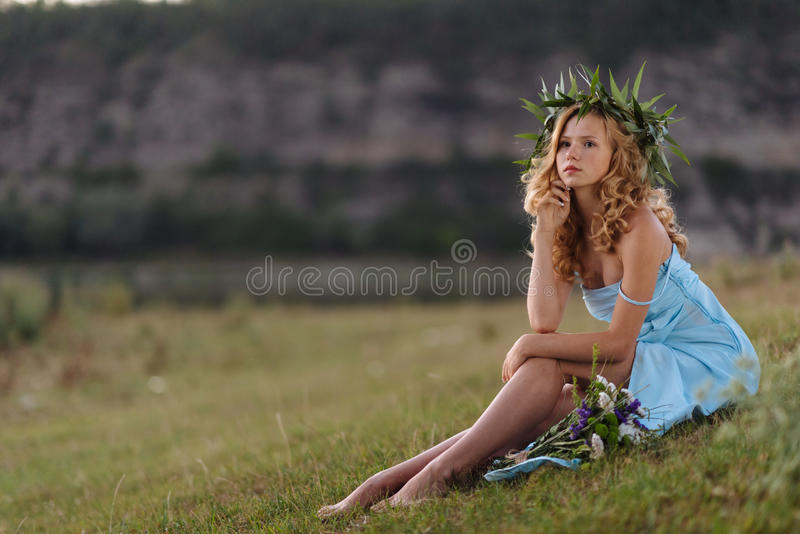 Κορίτσι στον πράσινο χορτοτάπητα στα πλαίσια των βράχων στοκ φωτογραφία με δικαίωμα ελεύθερης χρήσης