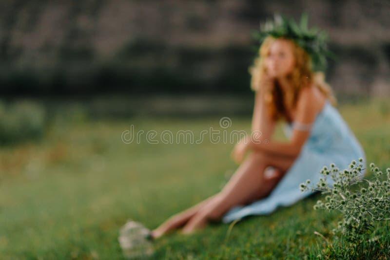 Κορίτσι στον πράσινο χορτοτάπητα στα πλαίσια των βράχων στοκ εικόνες