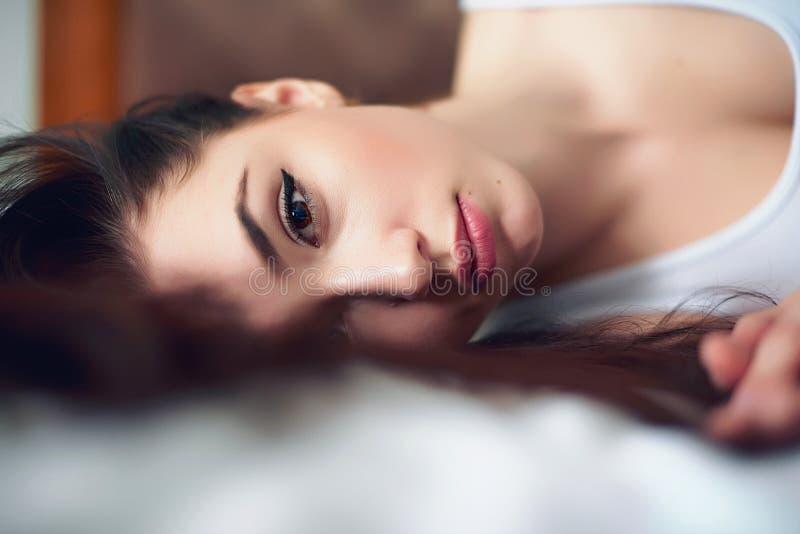Κορίτσι στο άσπρο άσπρο κρεβάτι τοπ κρεβατοκάμαρων στοκ εικόνα