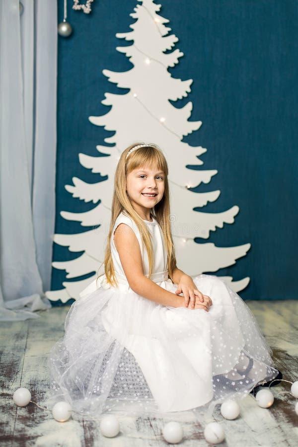 Κορίτσι στο άσπρο φόρεμα στο υπόβαθρο του χριστουγεννιάτικου δέντρου στοκ εικόνες