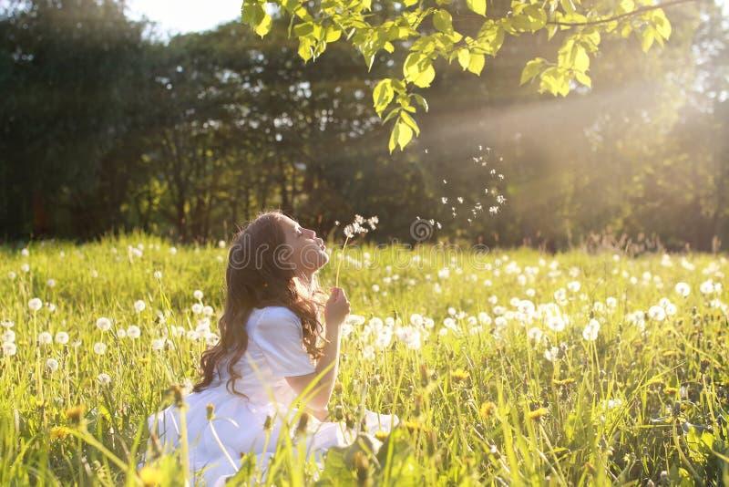 Κορίτσι στο άσπρο dundelion χτυπήματος φορεμάτων στοκ φωτογραφία
