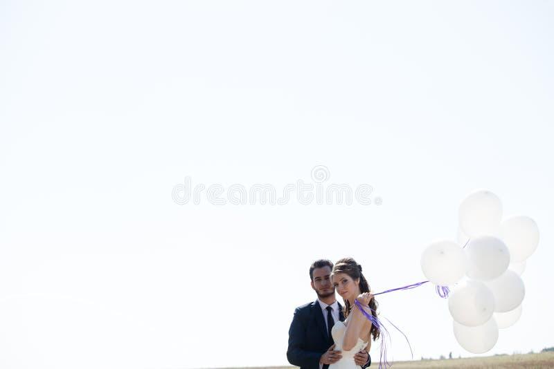 Κορίτσι στο γαμήλιο φόρεμα και husbad με ballons στα χέρια στοκ εικόνα με δικαίωμα ελεύθερης χρήσης