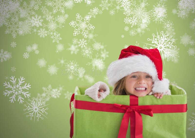Κορίτσι στο γκρίζο κλίμα μέσα στο κιβώτιο δώρων με το καπέλο και snowflakes Χριστουγέννων Santa στοκ φωτογραφία