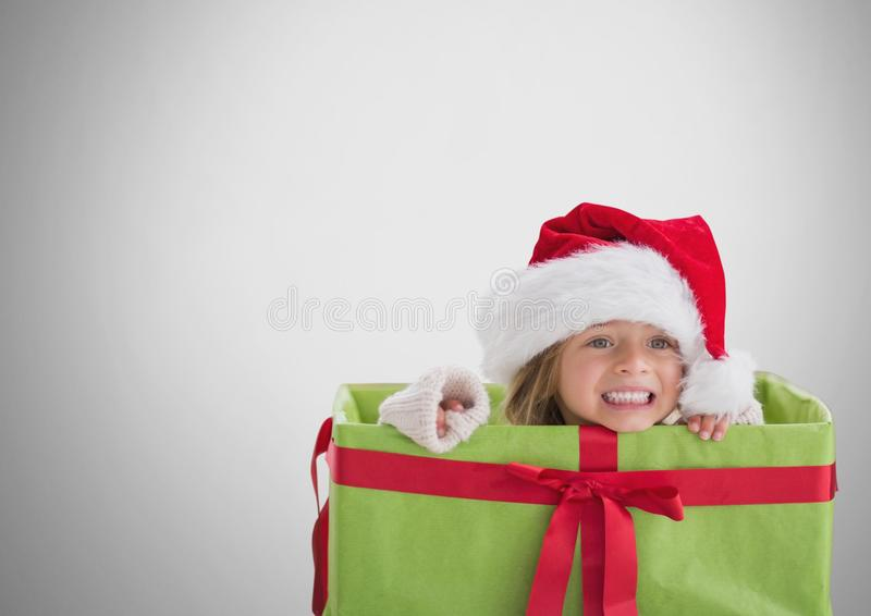 Κορίτσι στο γκρίζο κλίμα μέσα στο κιβώτιο δώρων με το καπέλο Χριστουγέννων Santa απεικόνιση αποθεμάτων