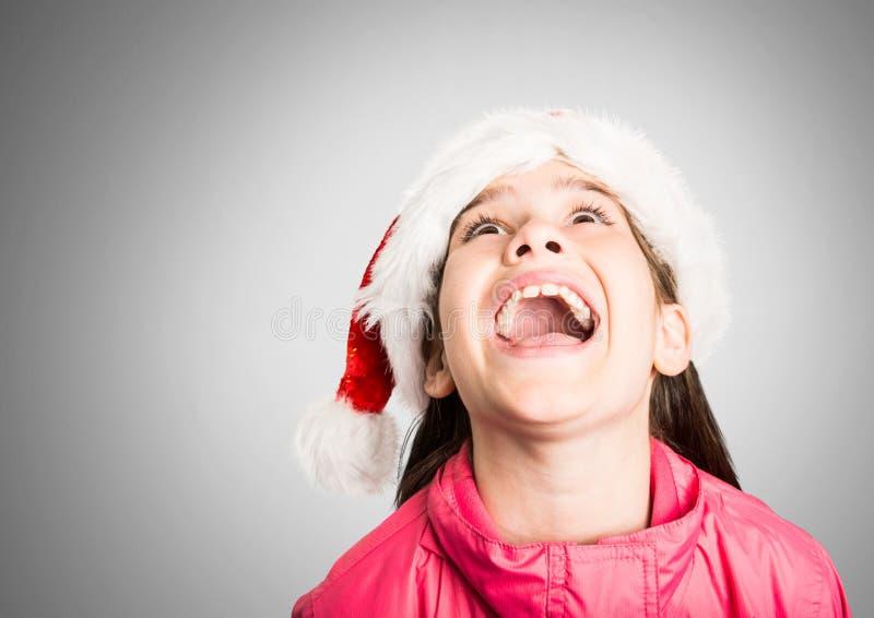 Κορίτσι στο γκρίζο κλίμα με την κατάπληκτη ευτυχή έκφραση και το καπέλο Χριστουγέννων Santa στοκ φωτογραφία