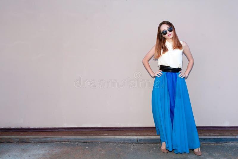 Κορίτσι στο γκρίζο υπόβαθρο σε ένα μπλε φόρεμα στοκ φωτογραφία με δικαίωμα ελεύθερης χρήσης