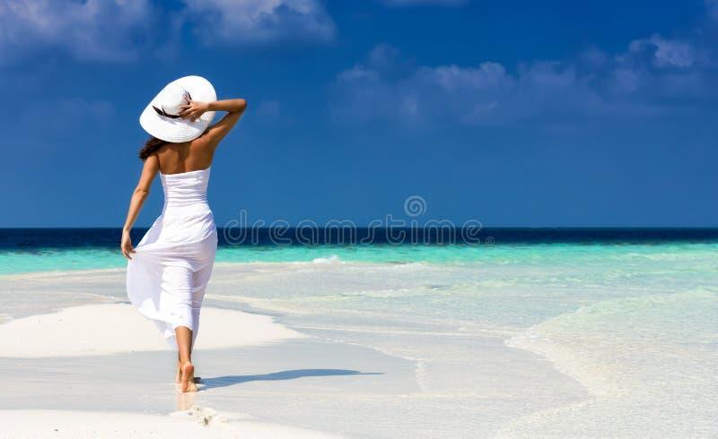 Κορίτσι στο λευκό σε μια αμμουδιά στις Μαλδίβες στοκ εικόνες