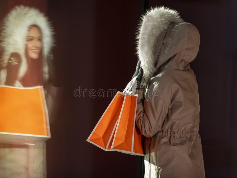 Κορίτσι στο κάτω σακάκι που εξετάζει την αντανάκλασή του στοκ φωτογραφία με δικαίωμα ελεύθερης χρήσης