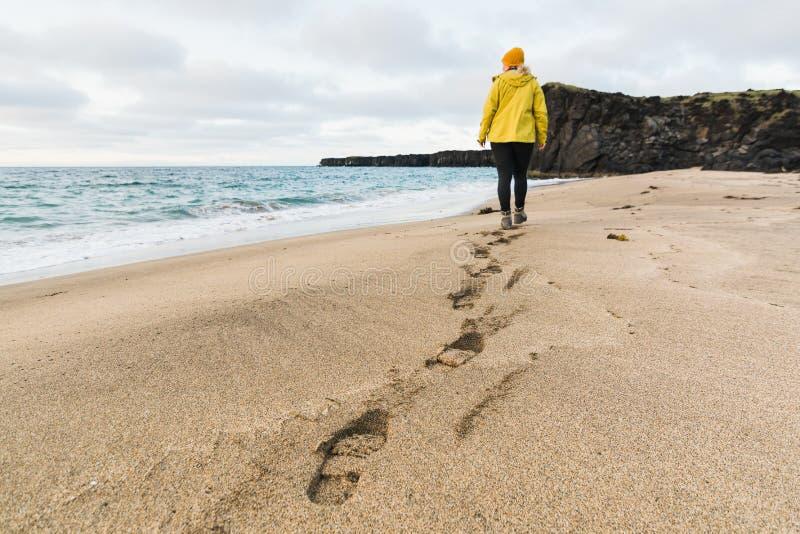 Κορίτσι στο κίτρινο αδιάβροχο που περπατά στην άμμο της παραλίας Skardsvik στο ηλιοβασίλεμα, χερσόνησος Snaefellsnes, Ισλανδία στοκ εικόνες με δικαίωμα ελεύθερης χρήσης