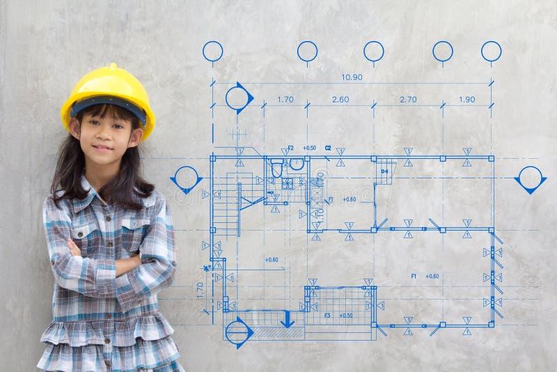 Κορίτσι στο κίτρινο κράνος που παρουσιάζει σχεδιάγραμμα που επισύρει την προσοχή στον τοίχο στοκ φωτογραφίες