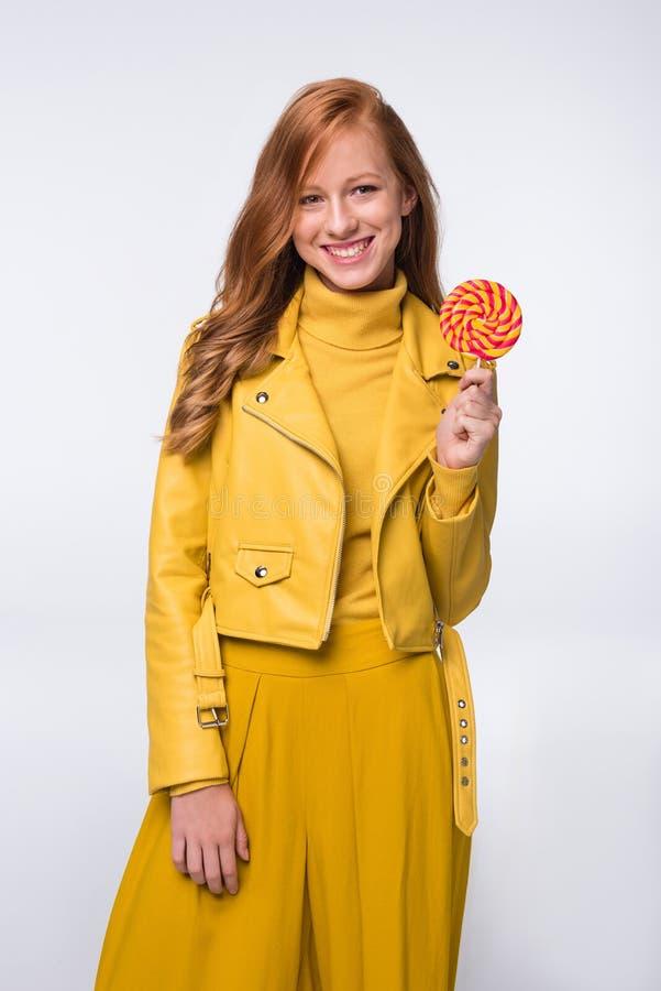 κορίτσι στο κίτρινο σακάκι δέρματος με το lollipop στοκ φωτογραφία με δικαίωμα ελεύθερης χρήσης
