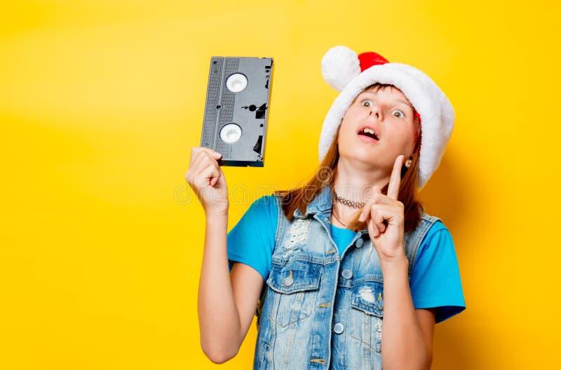 Κορίτσι στο καπέλο Χριστουγέννων με το VHS στοκ εικόνα