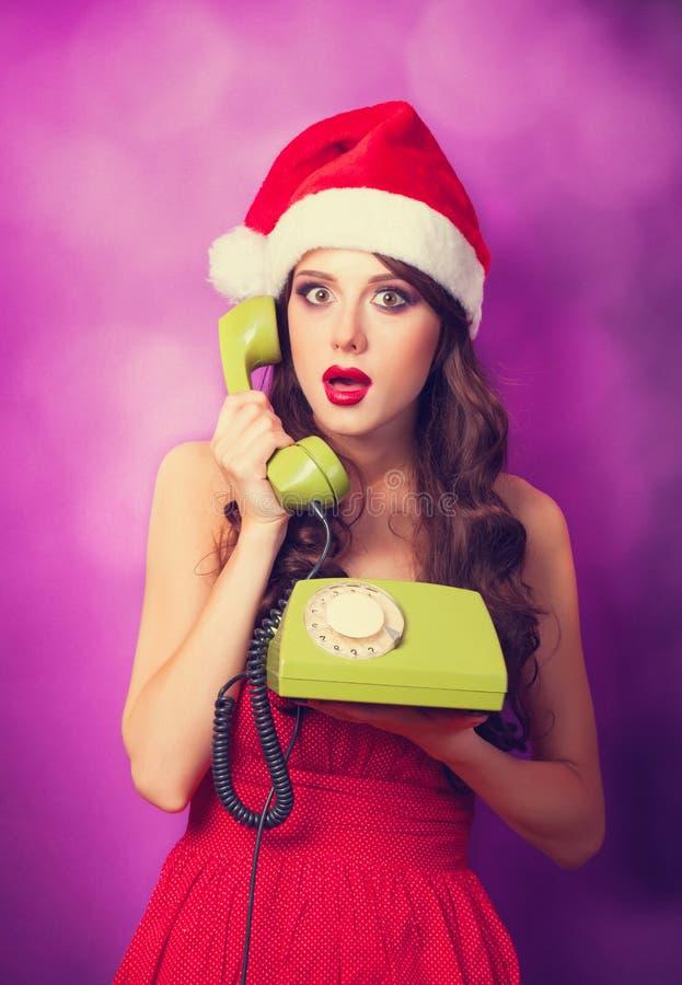 Κορίτσι στο καπέλο Χριστουγέννων με το πράσινο τηλέφωνο στοκ εικόνες