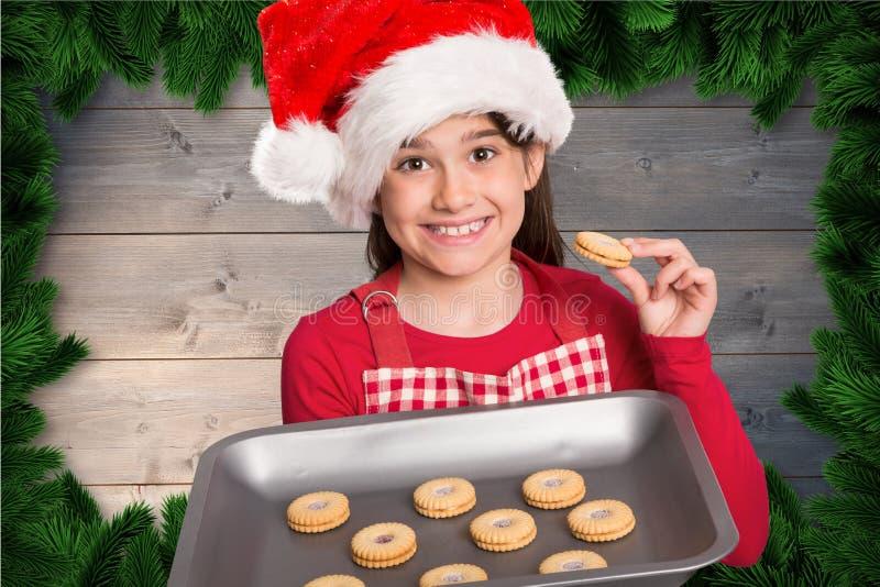 Κορίτσι στο καπέλο santa που κρατά έναν δίσκο με τα πρόσφατα ψημένα μπισκότα στοκ φωτογραφίες με δικαίωμα ελεύθερης χρήσης