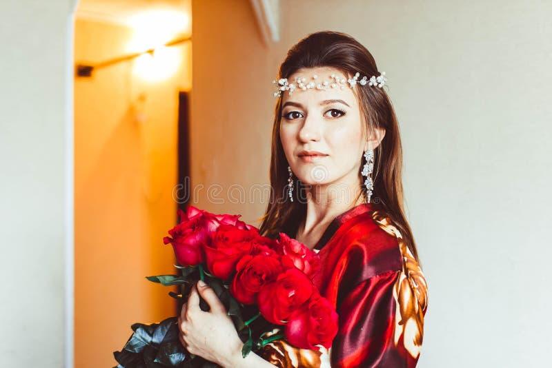 Κορίτσι στο κόκκινο με τα τριαντάφυλλα στοκ φωτογραφίες