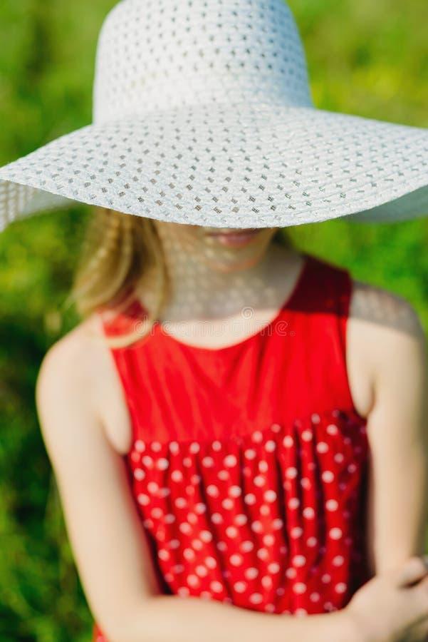 Κορίτσι στο κόκκινο φόρεμα και λευκό καπέλο με το μεγάλο χείλο στοκ φωτογραφία