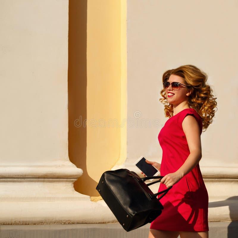 Κορίτσι στο κόκκινο φόρεμα και με την καθιερώνοντα τη μόδα τσάντα και το τηλέφωνο στοκ εικόνα