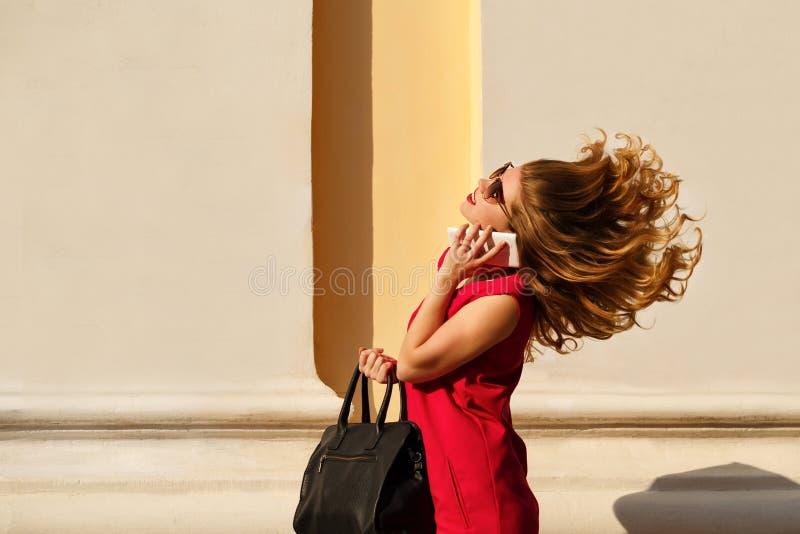 Κορίτσι στο κόκκινο φόρεμα και με την καθιερώνουσα τη μόδα τσάντα, τηλέφωνο στοκ εικόνες
