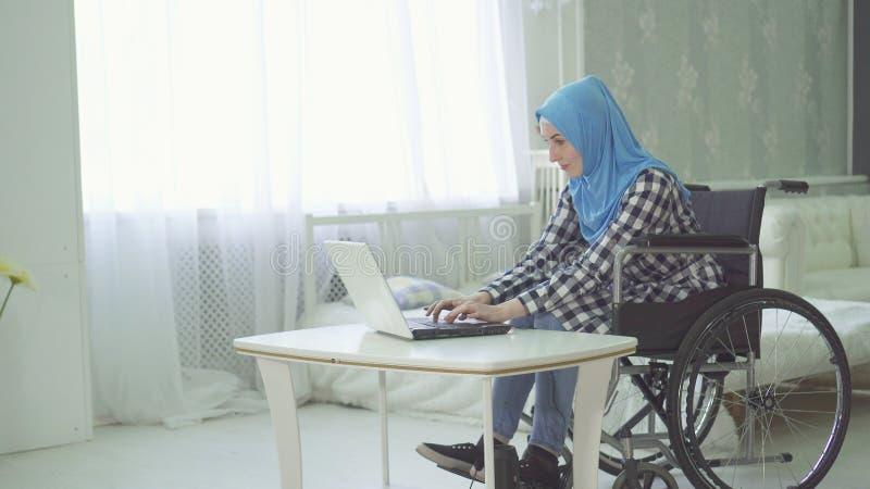 Κορίτσι στο με ειδικές ανάγκες άτομο hijab σε μια αναπηρική καρέκλα που χρησιμοποιεί ένα lap-top στοκ εικόνες