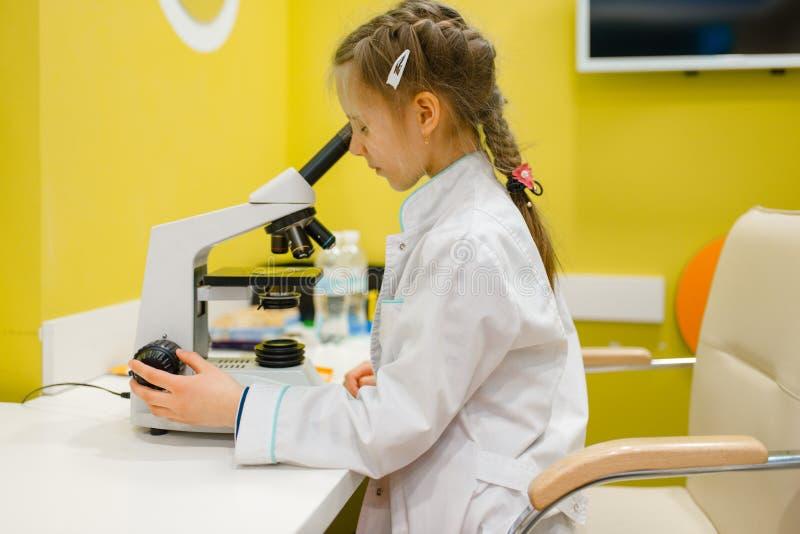 Κορίτσι στο μικροσκόπιο, παίζοντας γιατρός, χώρος για παιχνίδη στοκ φωτογραφία με δικαίωμα ελεύθερης χρήσης