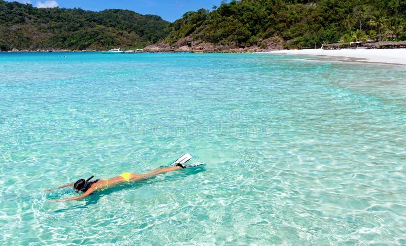 Κορίτσι στο μπικίνι που κολυμπά με αναπνευτήρα στα τροπικά νερά στοκ φωτογραφία