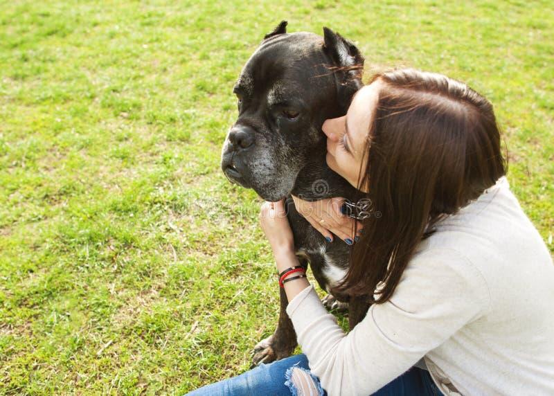 Κορίτσι στο πάρκο που περπατά με το μεγάλο κάλαμο Corso σκυλιών τους στοκ εικόνα με δικαίωμα ελεύθερης χρήσης