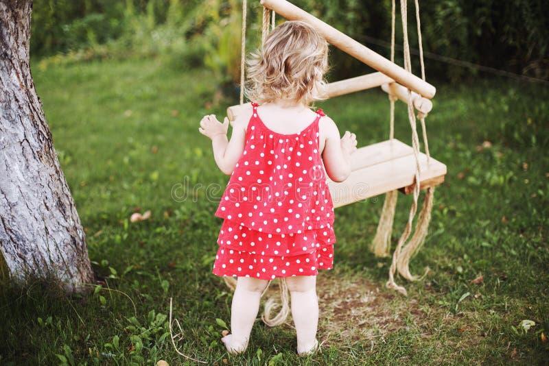 Κορίτσι στο παιχνίδι κήπων με την ταλάντευση Παιχνίδι μωρών στον κήπο στοκ φωτογραφίες