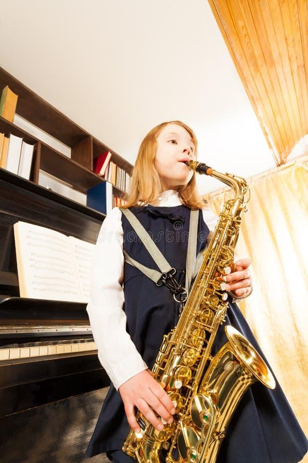 Κορίτσι στο παιχνίδι σχολικών στολών στο saxophone alto στοκ εικόνες