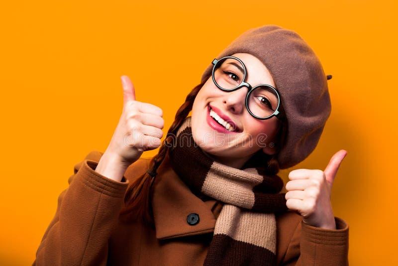 Κορίτσι στο παλτό και μαντίλι στο κίτρινο υπόβαθρο στοκ φωτογραφία με δικαίωμα ελεύθερης χρήσης