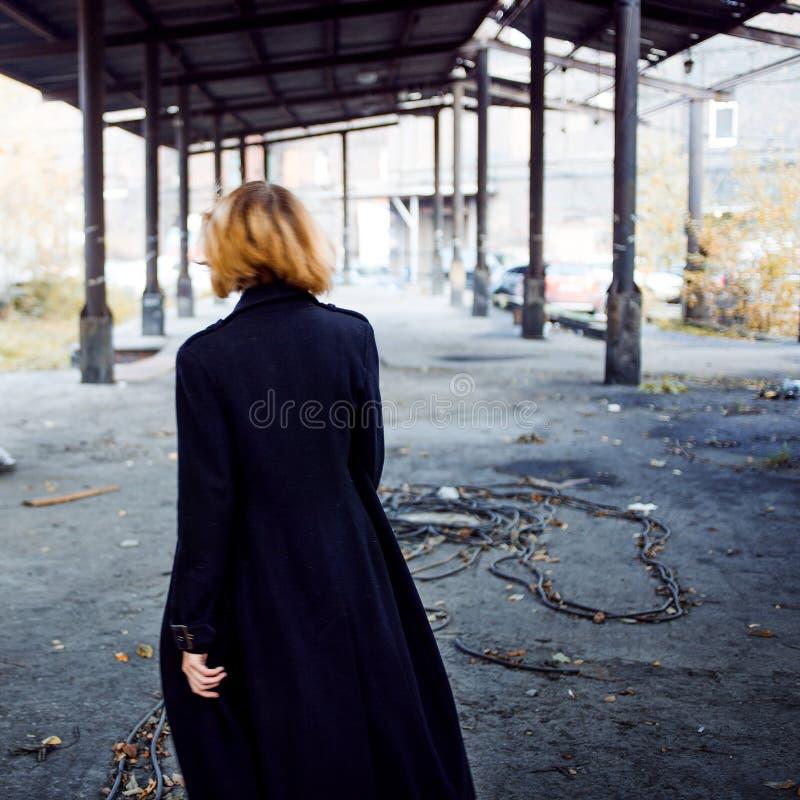 Κορίτσι στο παλτό, ένα στην εγκληματική περιοχή, πλάτη στοκ φωτογραφία με δικαίωμα ελεύθερης χρήσης