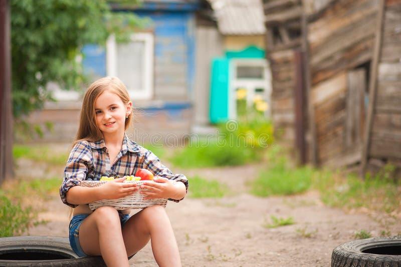 Κορίτσι στο πουκάμισο και σορτς με ένα καλάθι των φρούτων Αγρότης κοριτσιών με τα μήλα και τα σταφύλια Έννοια των οικολογικών τρο στοκ φωτογραφίες