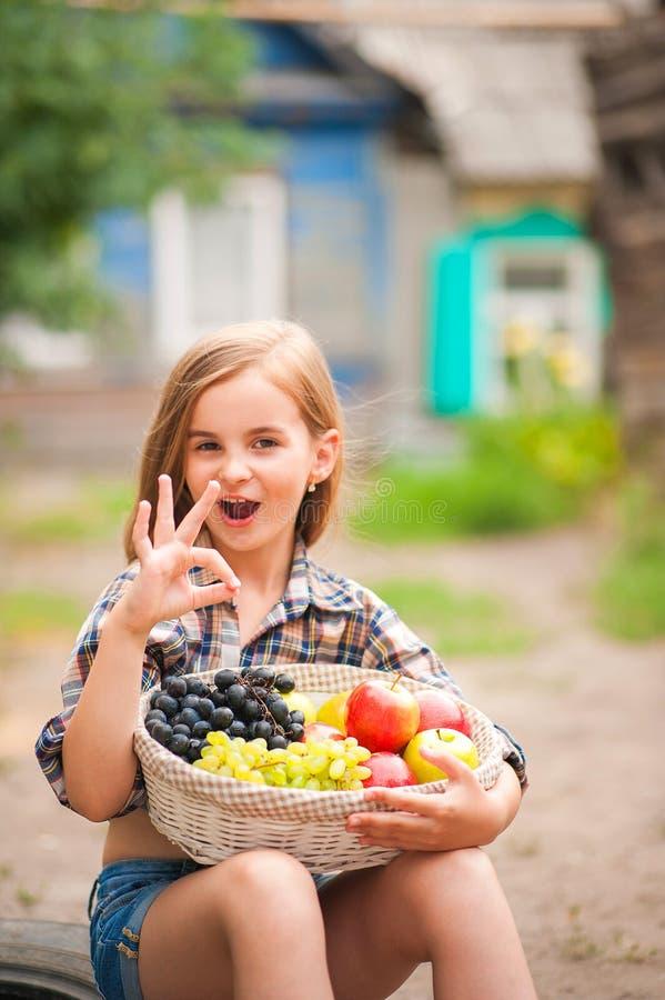 Κορίτσι στο πουκάμισο και σορτς με ένα καλάθι των φρούτων Αγρότης κοριτσιών με τα μήλα και τα σταφύλια Έννοια των οικολογικών τρο στοκ εικόνα