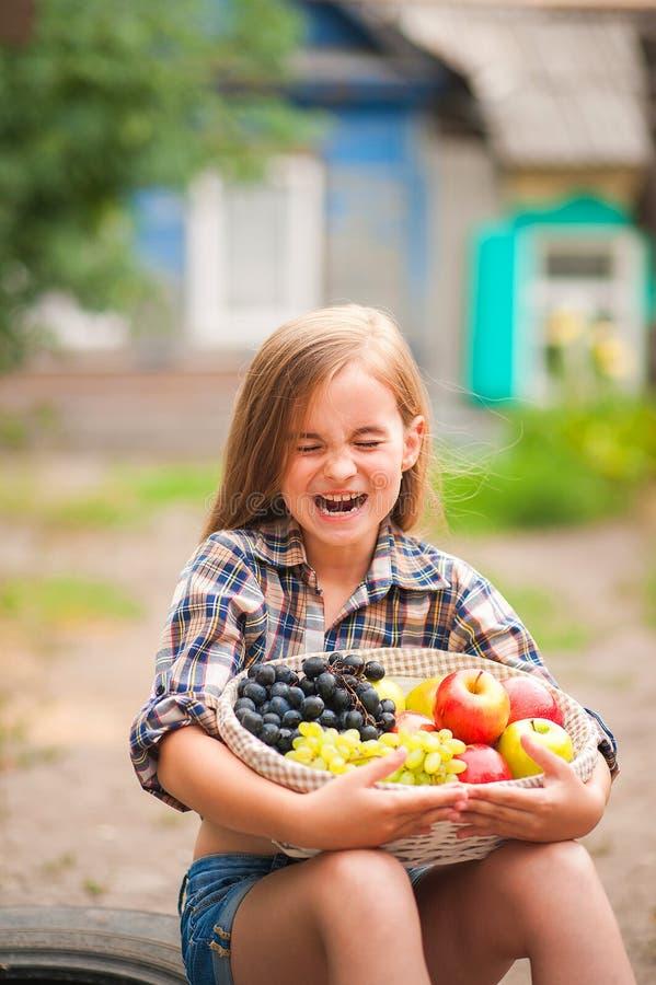 Κορίτσι στο πουκάμισο και σορτς με ένα καλάθι των φρούτων Αγρότης κοριτσιών με τα μήλα και τα σταφύλια Έννοια των οικολογικών τρο στοκ εικόνα με δικαίωμα ελεύθερης χρήσης