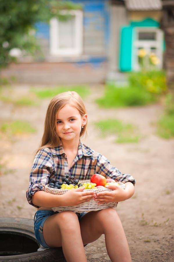 Κορίτσι στο πουκάμισο και σορτς με ένα καλάθι των φρούτων Αγρότης κοριτσιών με τα μήλα και τα σταφύλια Έννοια των οικολογικών τρο στοκ φωτογραφίες με δικαίωμα ελεύθερης χρήσης