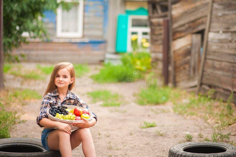 Κορίτσι στο πουκάμισο και σορτς με ένα καλάθι των φρούτων Αγρότης κοριτσιών με τα μήλα και τα σταφύλια Έννοια των οικολογικών τρο στοκ φωτογραφία με δικαίωμα ελεύθερης χρήσης