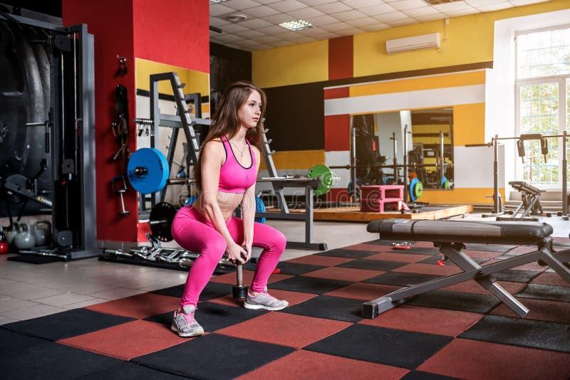 Κορίτσι στο ρόδινο αθλητικό φόρεμα που κάνει τα exercices στοκ εικόνες