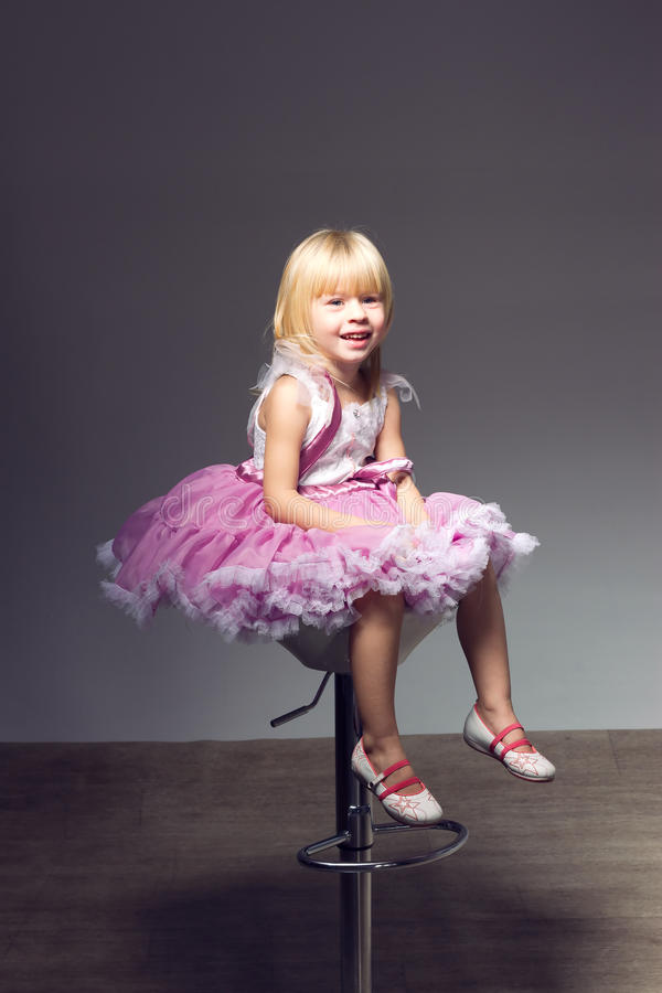 Κορίτσι στο ρόδινο tutu, στούντιο που κάθεται μια έδρα στοκ εικόνα