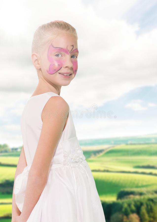 Κορίτσι στο ρόδινο facepaint ενάντια στους τομείς με τη φλόγα στοκ φωτογραφία