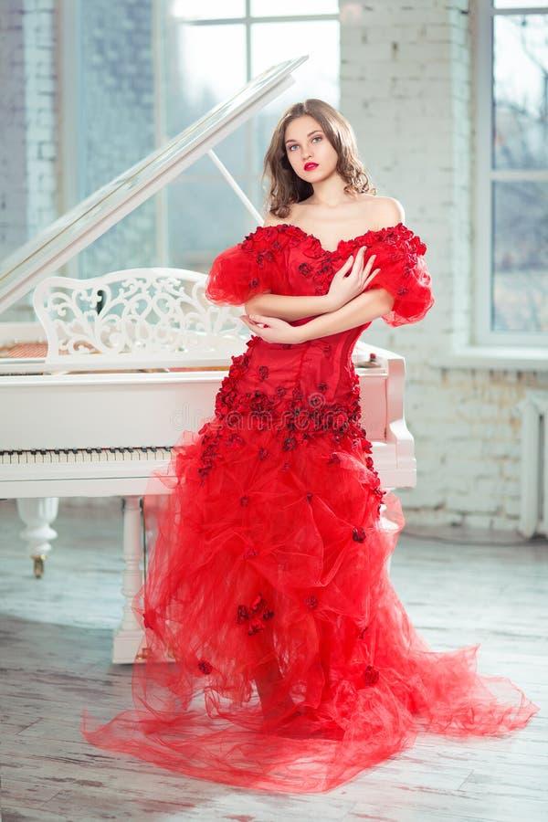 Κορίτσι στο φόρεμα βραδιού που στέκεται δίπλα σε ένα μεγάλο άσπρο μεγάλο πιάνο στοκ εικόνα