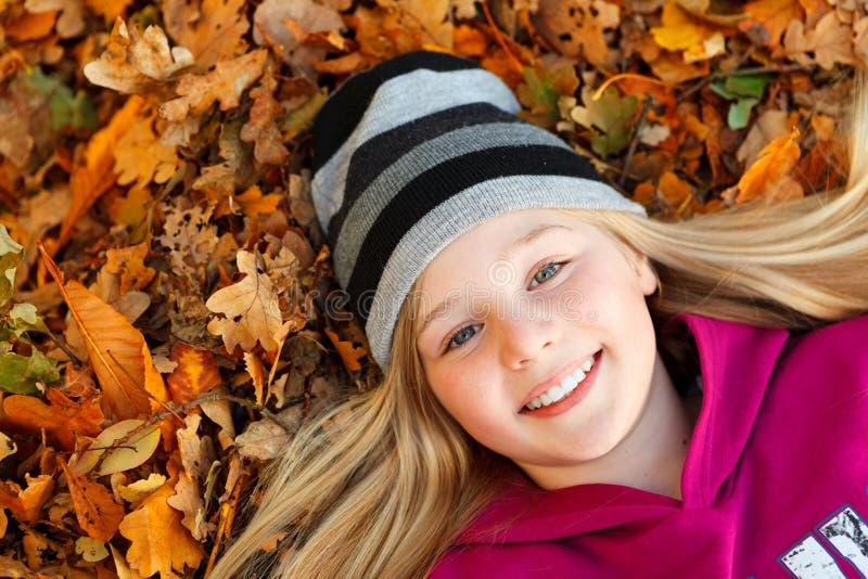 Κορίτσι στο χαμόγελο φύλλων φθινοπώρου στοκ εικόνες