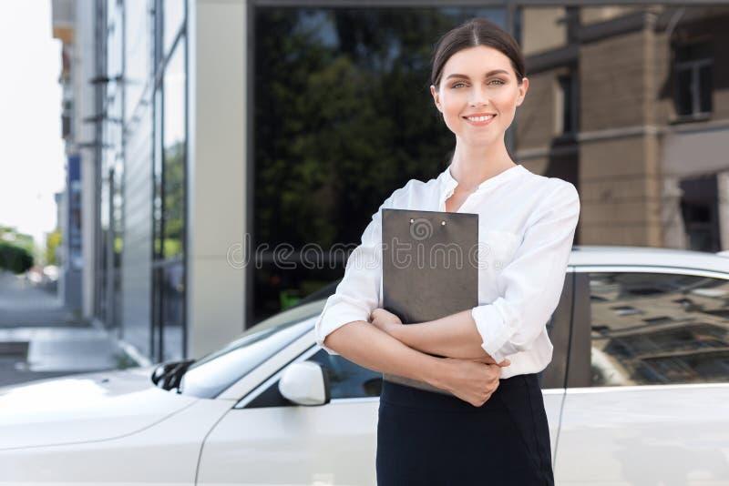 Κορίτσι συμβούλων με τα έγγραφα που στέκονται κοντά στο νέο αυτοκίνητο στοκ φωτογραφία με δικαίωμα ελεύθερης χρήσης