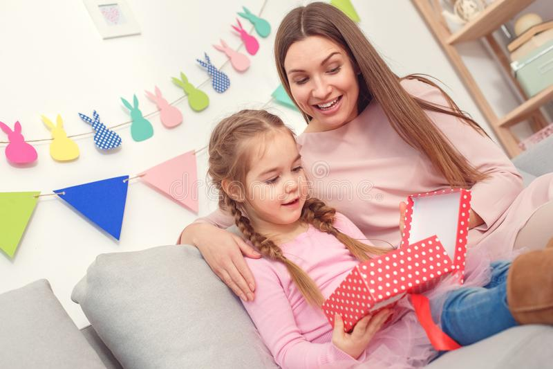 Κορίτσι συνεδρίασης έννοιας εορτασμού μητέρων και κορών μαζί στο σπίτι που φαίνεται εσωτερικό κιβώτιο δώρων έκπληκτο στοκ φωτογραφία με δικαίωμα ελεύθερης χρήσης