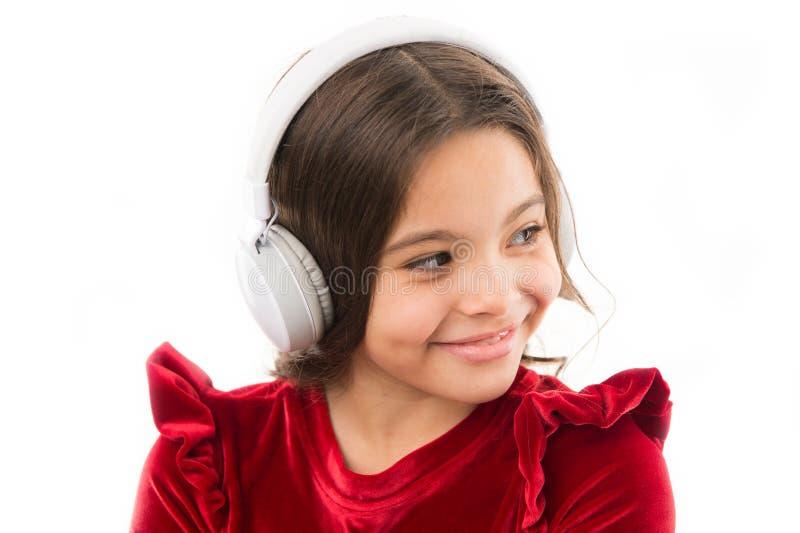 Κορίτσι σύγχρονα ακουστικά λίγης παιδιών μουσικής χρήσης Αφουγκραστείτε τα ελεύθερα νέα και επερχόμενα δημοφιλή τραγούδια αυτή τη στοκ φωτογραφία