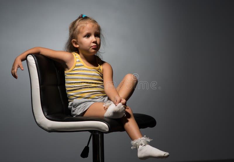 Κορίτσι τέσσερα έτη σε μια καρέκλα στοκ εικόνα