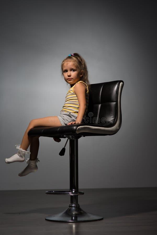 Κορίτσι τέσσερα έτη σε μια καρέκλα στοκ φωτογραφίες
