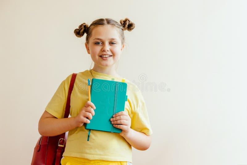 Κορίτσι της ηλικίας με ένα σακίδιο πλάτης βιβλίων, μανδρών και σχολείων κίτρινο sportswear στοκ εικόνα