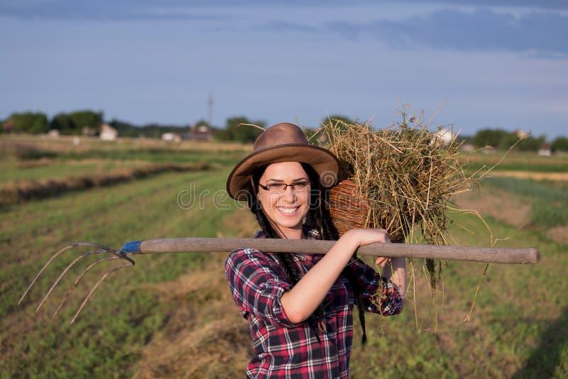 Κορίτσι της Farmer με το καλάθι και hayfork στοκ φωτογραφία