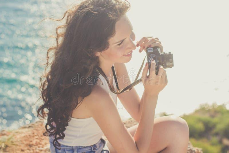Κορίτσι τουριστών που κάνει τη φωτογραφία από την παλαιά κάμερα στην κορυφή βουνών στοκ εικόνα