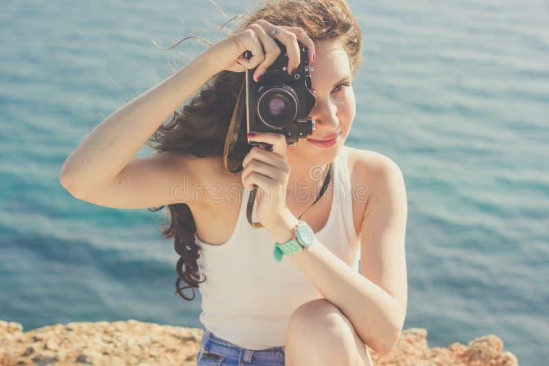 Κορίτσι τουριστών που κάνει τις εικόνες από την παλαιά κάμερα στην κορυφή βουνών στοκ εικόνα με δικαίωμα ελεύθερης χρήσης